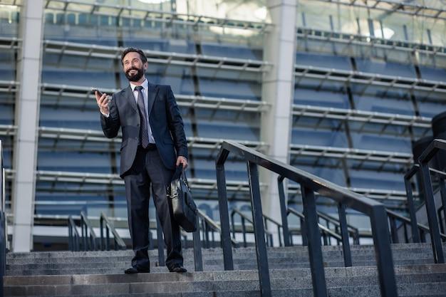 アーバンビルディング。都会の環境に立っている間彼の電話を使用して楽観的な笑顔のビジネスマン