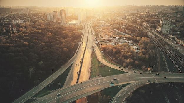 Городской автомобильный транспортный затор с воздуха. city street motion lane, обзор навигации по приводам. оживленный городской скоростной маршрут с лесным парком вокруг. концепция путешествия drone flight shot