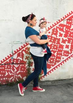 スリングキャリアの母と幼児の女の子の都会的なカジュアルな家族の外観