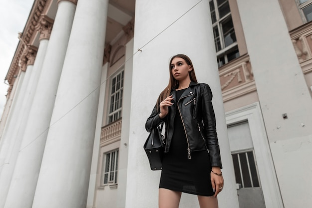 Urban cute young woman in a fashionable black leather jacket in a vintage black dress with a stylish bag stands on the street near a white building on an autumn day. modern girl on a walk. youth style
