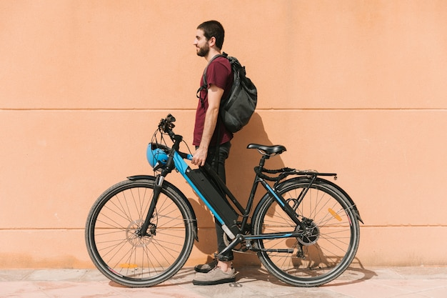 Urban cyclist standing next to e-bike