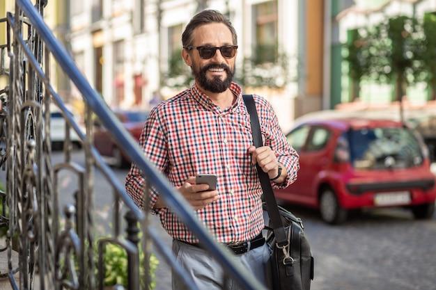 都会の日。通りを歩きながら笑っている陽気な喜んでひげを生やした男