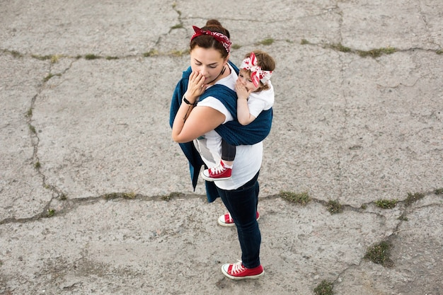 Urban family look of mother and baby girl in sling carrier wrap