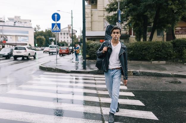 Городская мода уверенно рок-стиль человек идет с гитарой. концепция жизни города музыкального образа жизни