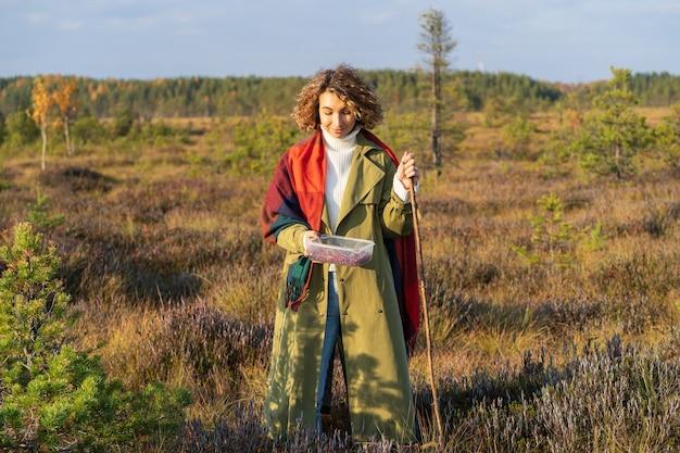 森の中でクランベリーを歩くトレンディな塹壕で秋の自然のスタイリッシュな若い女性のアーバンファッション