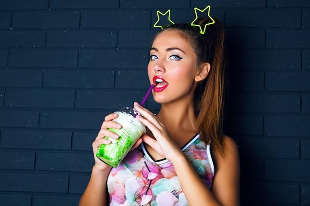 Ritratto di moda urbana di donna bruna con coda di cavallo alta, trucco alla moda, indossa una camicia stampata e un divertente accessorio da festa sulla testa, bevendo un gustoso frappè verde dolce, stile urbano.