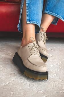 Городская модная обувь. повседневные кроссовки на ногах девочки-подростка в джинсовых джинсах. подросток сидит на красном старом кожаном кресле, бетонный фон, фото