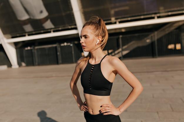 Городская женщина фитнеса протягивая на спортивной солнечной площади. фитнес спортсмен, тренирующийся на улице