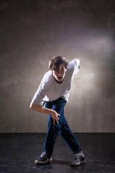 グランジコンクリートの壁の背景のテクスチャジャンプとダンスとアーバンヒップホップダンサー