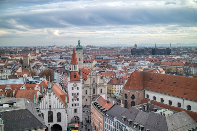 Urban landscape, aerial panoramic view above roofs of retro houses historical part of munich, germany on a background of cloudy sunset sky.