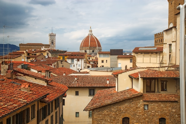 The urban landscape of florence. top view of the cathedral of saint mary of the flower and the tiled roofs of houses.