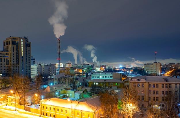 Городской пейзаж района в москве с традиционной современной архитектурой в зимнюю ночь. трубы котельной с загрязнением воздуха