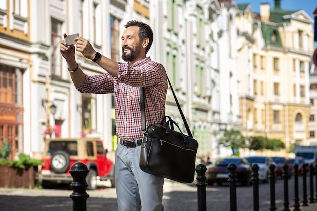 都会暮らし。写真を作りながら通りに立っているうれしそうな喜びの男