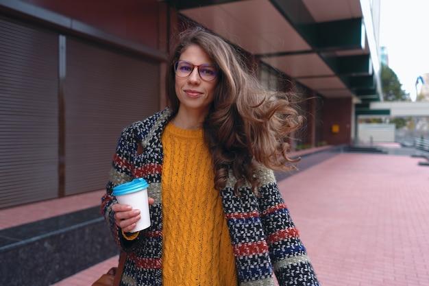 外出先での都会のライフスタイルとコーヒー。屋外でコーヒーを飲むコートを着たスタイリッシュで若い女性。街の通りを歩くモダンな都会の衣装とメガネのカジュアルな女の子。
