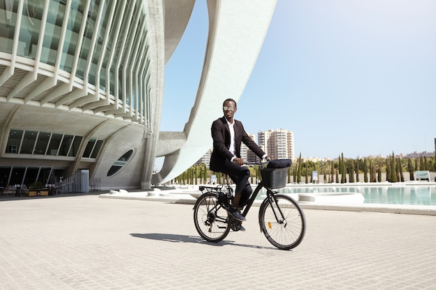 Urban lifestyle, ecology and transportation concept. fashionable modern ecologically friendly young afro american businessman wearing trendy round shades and formal suit cycling to work on bicycle