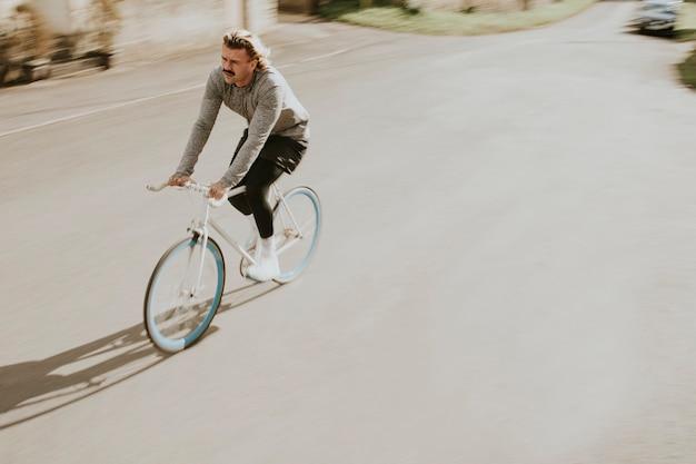 路上で自転車に乗って口ひげを持つ都会の男