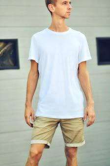 옷의 도시 모형. 빈 티셔츠와 갈색 반바지를 입은 세련된 남자가 검은 창문이있는 흰색 질감 벽 근처에 서 있습니다. 당신이 디자인을위한 템플릿 준비.