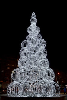 밤 도시에 조명이 있는 도시의 현대적인 크리스마스 트리