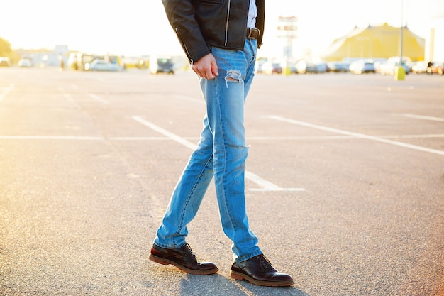Urban outdoor fashion portrait of young stylish hipster man wearing leather biker jacket denim pants and vintage shoes posing at countryside parking evening sunlight.