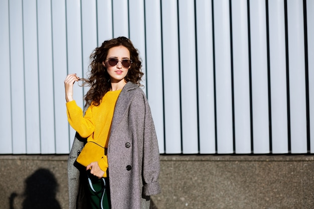 Urban portrait of cute hipster woman walking down the street,wearing trendy outfit. space for text