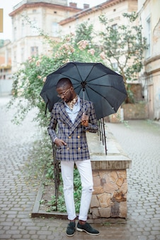 Urban portrait of handsome african american businessman standing in city center in cloudy weather under black umbrella dressed in formal clothes.