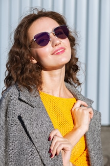Urban portrait of happy fashionable woman walking down the street, posing near the shutters