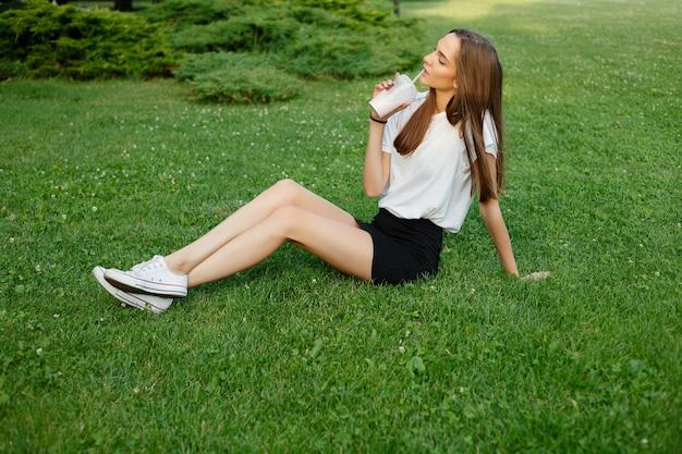 Городской портрет молодой привлекательной брюнетки в белой футболке, пьющей молочный коктейль