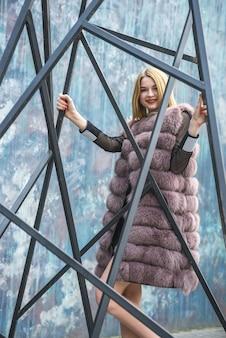 毛皮のコートを着た若い女性の都会の肖像画。街の通りでポーズをとってエレガントなドレスの女性