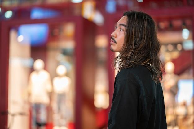 긴 머리를 가진 젊은 남자의 도시 초상화