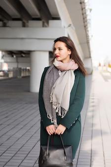 暖かいコートを着て、黒い財布を持っている若いモデルの都市の肖像画。テキスト用のスペース