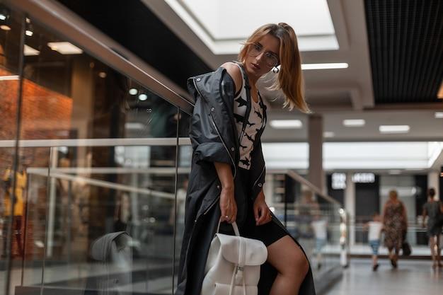 쇼핑몰에서 포즈를 취하는 유행 헤어 스타일으로 빈티지 선글라스에 세련된 옷을 입고 도시 예쁜 젊은 여자. 나가서는 아름다운 소녀 패션 모델 실내. 아메리칸 모던 스타일.