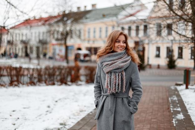 니트 따뜻한 스카프에 회색 세련된 코트에 아름다운 미소로 도시 예쁜 젊은 여자가 겨울 날에 빈티지 건물 근처의 도시를 산책합니다
