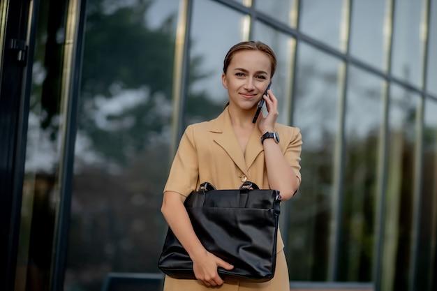 그녀의 휴대 전화를 사용하여 도시를 걷는 도시 부동산. 비즈니스 우먼 스마트 폰을 사용합니다.