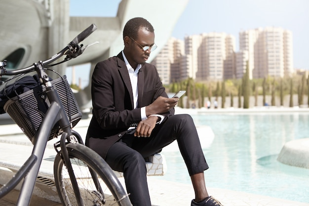 Urban shot of confident african american businessman wearing round sunglasses and elegant black suit sitting outdoors with his bicycle, using mobile phone, checking e-mail and dealing business issues