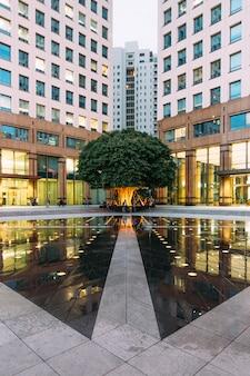 Городская площадь фонтана с большим зеленым деревом в углу с людьми.