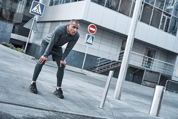 도시 스포츠 청년은 도시에서 달리기 전에 워밍업을 하고 있다
