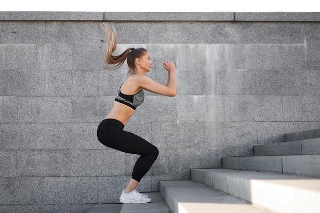 도시 스포티 한 여자 훈련. 도시 계단에 쪼그리고 점프하는 여자 선수