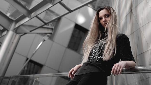 Блондинка в городском стиле с суровым взглядом стоит на фоне современного здания. в черной рубашке. сила девушки и концепция субкультуры.