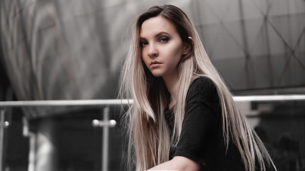 Urban style blonde girl with a stern look standing on the background of a modern building. wearing black shirt. girl power and subculture concept.