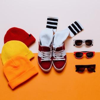 アーバンスタイルの服。スケートボードのファッション衣装。スニーカー、ストッキング、帽子。サングラス。明るいトレンドに焦点を当てる