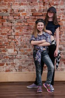 도시 스타일. 힙합의 우정. 스튜디오에서 세련된 여성 청소년, 춤의 행복, 여유 공간이있는 벽돌 벽 배경. 행복한 거리 생활, 아름다운 자매 개념