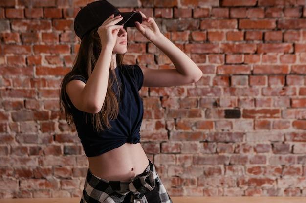 도시 스타일. 현대 십대 하위 문화. 댄스 스튜디오, 여유 공간이있는 벽돌 벽 배경에서 세련 된 어린 소녀. 삶을위한 브레이크 댄스, 스트리트 힙합, 패션 컨셉