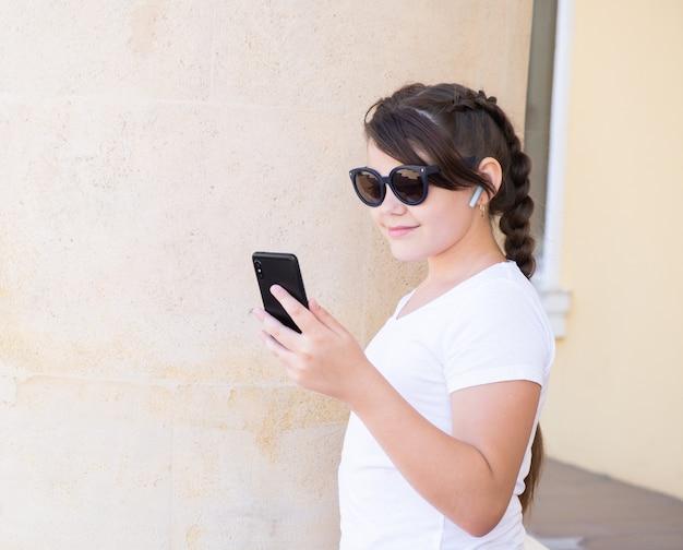 都会のスタイリッシュな10代の女の子が携帯電話でビデオ通話、ハンズフリー、友達との会話