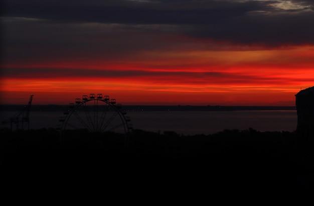 Городской восход солнца в городе с колесом обозрения на заднем плане.