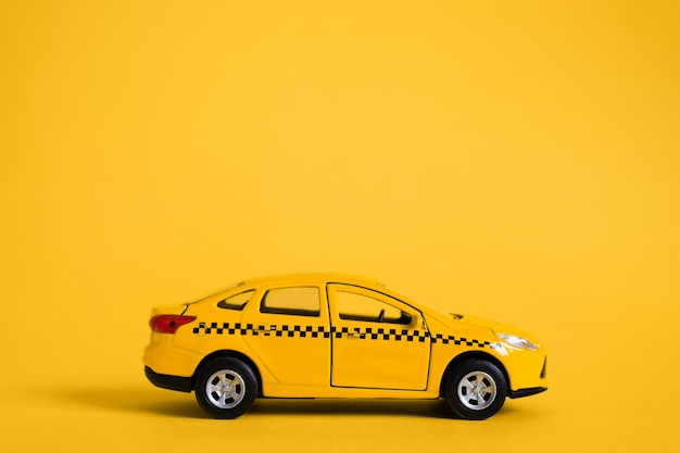Urban taxi and delivery service concept. toy yellow taxi car model. copy space for text, banner. online mobile application order taxi service.