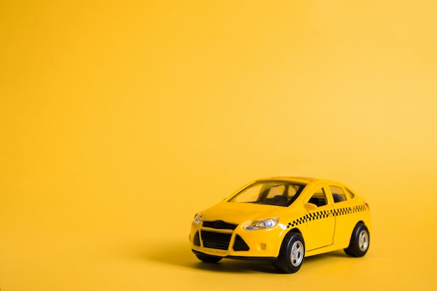 Urban taxi and delivery service concept. toy yellow taxi car model.