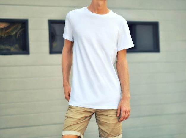 옷의 도시 템플릿입니다. 흰색 티셔츠와 갈색 반바지를 입은 슬림 한 남자가 검은 창문이있는 흰색 질감 벽 근처에 서 있습니다. mockup은 쇼케이스에 사용할 수 있습니다.