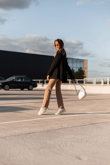 スタイリッシュなカジュアルな服と靴のバッグを持った都会のトレンディな若い女性がモールに歩いて行きます。晴れた夏の日に屋外駐車場でポーズをとる現代の女の子。エレガントな外観。
