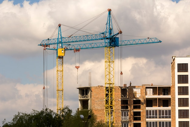Urban view of silhouettes of two high industrial tower cranes above green tree tops working at construction of new brick building with workers in hard hats on it against bright blue sky background.