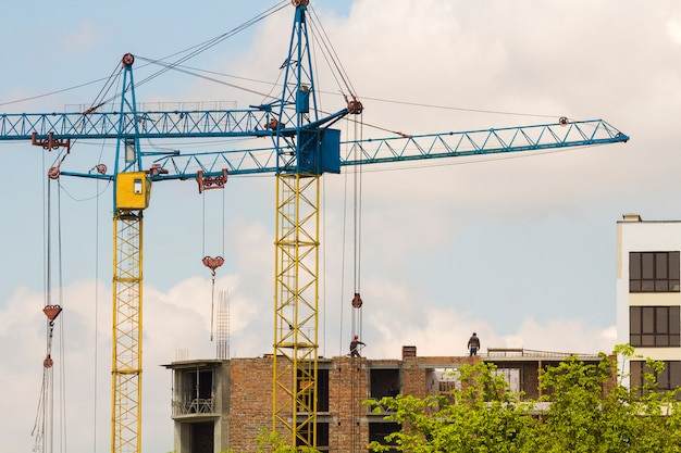 Urban view of silhouettes of two high industrial tower cranes working at construction of new brick building with workers in hard hats on it against bright blue sky and green top trees background.